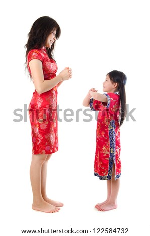 Chinese parent and child in traditional Chinese cheongsam greeting, isolated on white background - stock photo