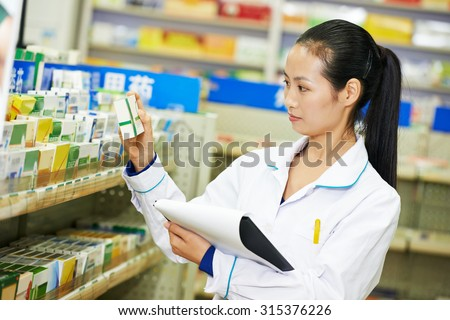 chinese pharmacist chemist woman choosing tablets in china pharmacy drugstore - stock photo