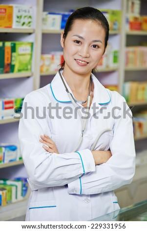chinese pharmacist chemist woman standing in china pharmacy drugstore - stock photo