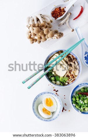 Chinese porcelain bowl of asian ramen soup with feta cheese, noodles, spring onion and mushrooms, served with turquoise chopsticks and sliced egg over white background. Top view - stock photo