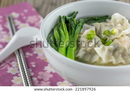 Chinese pork and shrimp dumplings with green vegetables in a broth. - stock photo