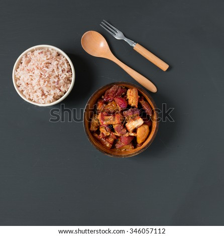 Chinese pork belly caramelized and braised in soy sauce with star anise, cinnamon and chilies. Overhead shot and eat with brown rice on black background - stock photo