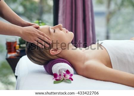 Chinese pretty woman receiving head massage in salon - stock photo