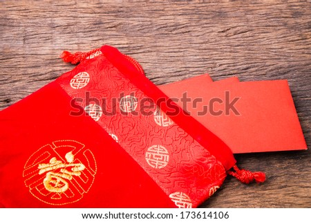 Chinese red pocket in Chinese red bag on wooden table - stock photo