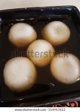 Chinese rice ball with ginger soup served in a black bowl