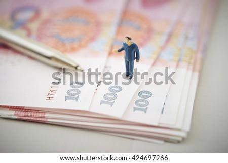 Chinese RMB bills, pen and miniature men - stock photo