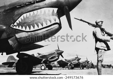 Chinese soldier guards a line of American P-40 fighter planes, ca. 1942. The shark-face fighters of the 'Flying Tigers' had a 12-to-1 victory ratio over the Japanese planes during World War 2. - stock photo