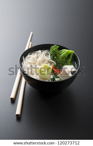 Chinese soup with noodles tofu and vegetables close up - stock photo