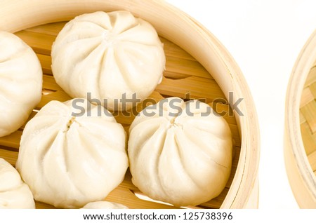 Chinese steamed buns in bamboo steamer basket isolated on white - stock photo