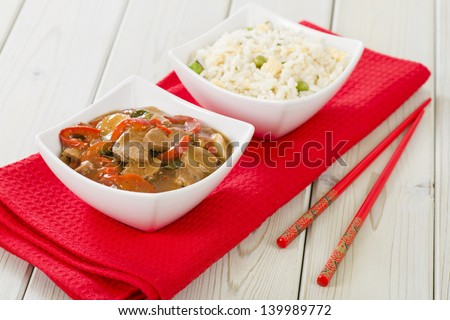 Chinese style pork with red peppers served with egg fried rice. - stock photo