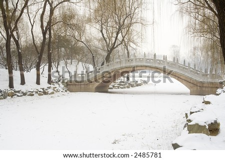 Chinese styled bridge over a frozen river in winter