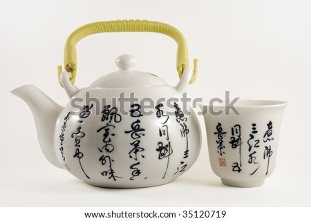 Chinese tea pot with tea cup with chinese writings - stock photo