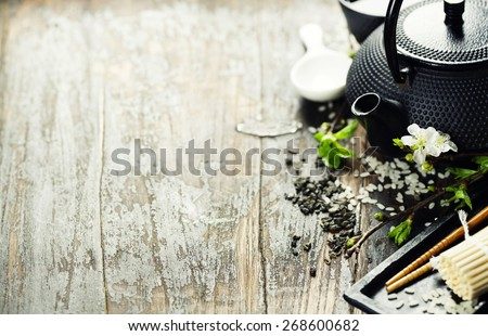 Chinese Tea Set,chopsticks and sakura branch on rustic wooden table - stock photo