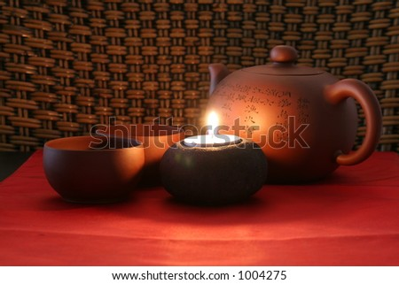 Chinese tea set highlighted with a candle. - stock photo