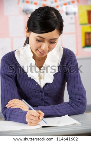 Chinese Teacher Sitting At Desk In School Classroom