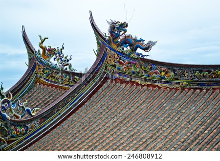 Chinese temple roofs. One blue and one yellow dragon on each roof. Phoenix and other historical characters along the edge of the roof all painted in red, yellow, blue, green and white colors. - stock photo