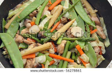 chinese vegetable and chicken stir-fry in skillet close-up - stock photo