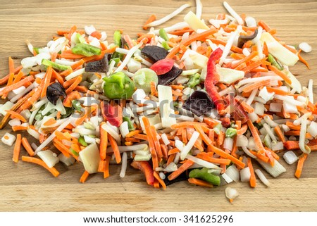 Chinese vegetables sliced in strips on wooden board. - stock photo