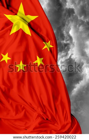 Chinese waving flag on a bad day - stock photo