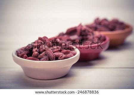 Chinese wolfberry(Lycium barbarum) on white background. goji berries. vitamin c fruit. goji in bowl - stock photo
