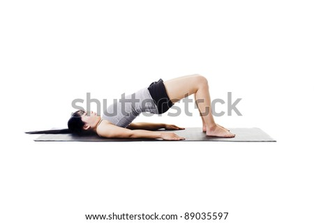 Chinese woman on a yoga mat doing the bridge pose. - stock photo