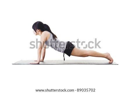 Chinese woman on a yoga mat doing the plank pose. - stock photo