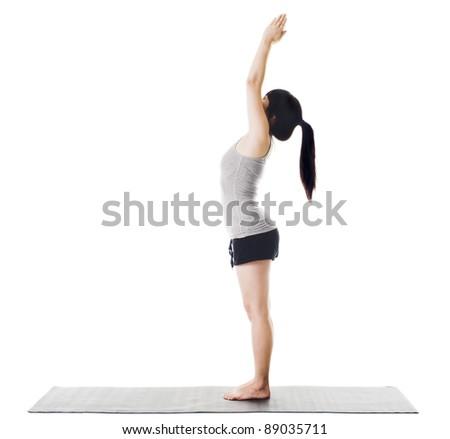 Chinese woman on a yoga mat doing the upward salute pose. - stock photo
