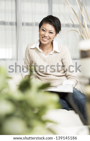 Chinese Woman reading a magazine while sitting on a sofa in her living room - stock photo