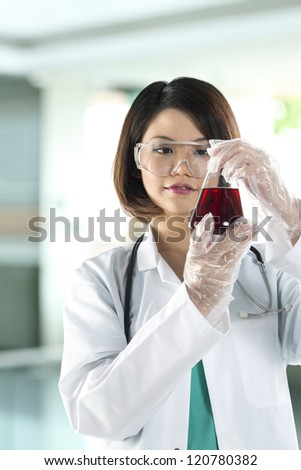 Chinese woman scientist or Doctor looking at a liquid solution. - stock photo