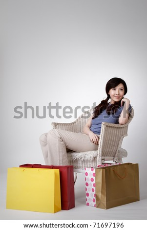 Chinese woman siting on chair and putting bags on ground. - stock photo
