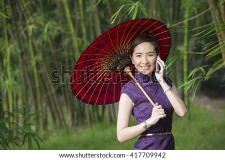 Chinese Woman talking on a Smart Phone and wearing a Cheongsam Chinese Dress with traditional umbrella. - stock photo