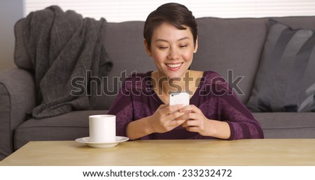 Chinese woman texting on smartphone by coffee table