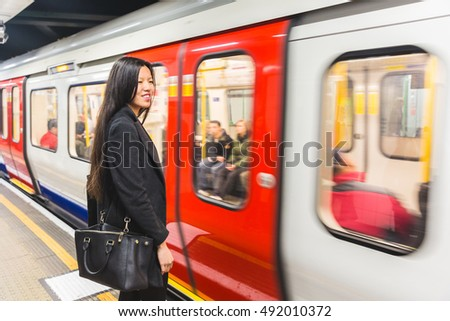 Chinese woman waiting at tube station. She is standing on the platform, with a blurred train passing on background. City lifestyle and transport concepts.