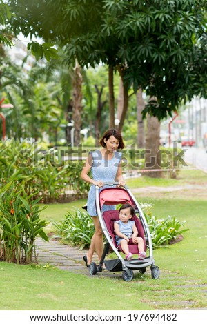 Chinese woman walking in the park with her daughter in the baby carriage - stock photo
