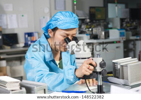 Chinese worker monitors the quality of the products by microscope on factory - stock photo