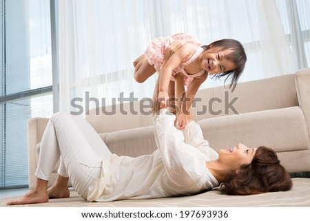 Chinese young lady playing with her daughter at home - stock photo