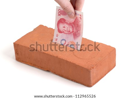 "Chinese Yuan bank note in a ""piggy bank"" or ""tissue box"" like brick - stock photo"