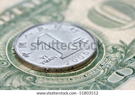 Chinese yuan coin on top of US dollas bank note. - stock photo