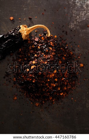 chipotle - jalapeno smoked chili flakes and whole on metal background - stock photo