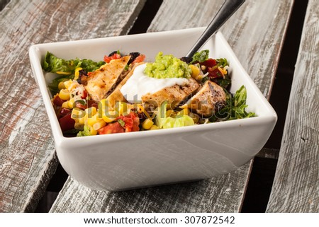 Chipotle seasoned homemade chicken and rice bowl on a weathered barn wood table side shot - stock photo
