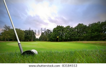chipping a golf ball onto the green with golf club at sunset - stock photo
