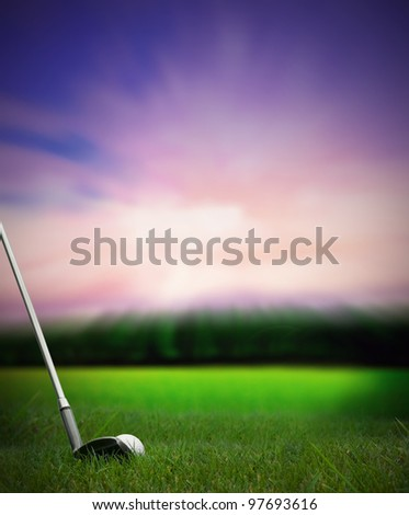 chipping a golf ball with club onto the green from fairway at sunset - stock photo
