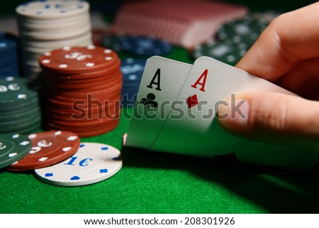 Chips and cards for poker in hand on green table - stock photo