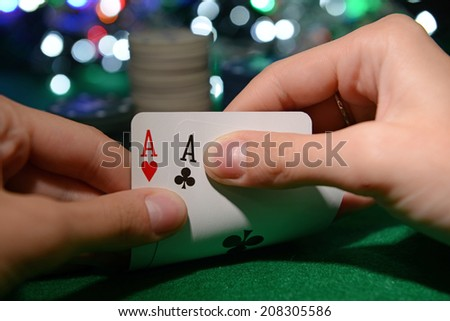 Chips and cards for poker in hands on green table