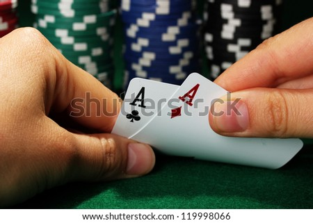 Chips and cards in hands on green table