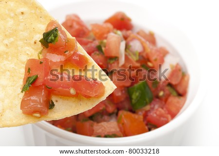 Chips and Fresh salsa in a bowl against a white background - stock photo