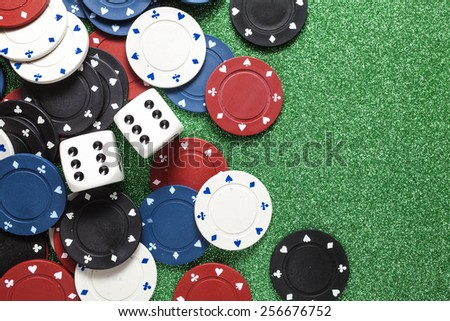 Chips for poker and dice on green background - stock photo