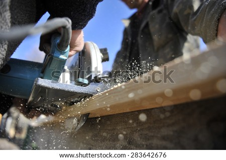 chips from a circular saw. Two men carpenters - stock photo