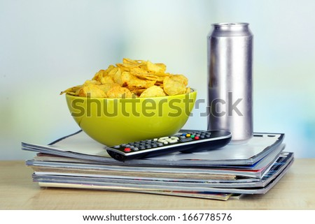 Chips in bowl, beer and TV remote on wooden table on room background - stock photo