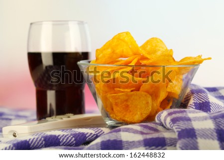 Chips in bowl, cola and TV remote on plaid on bright background - stock photo